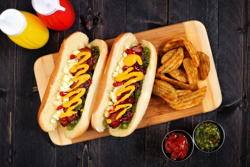 Os cachorros quentes e a batata firmam na placa de madeira, cena aérea imagem de stock royalty free