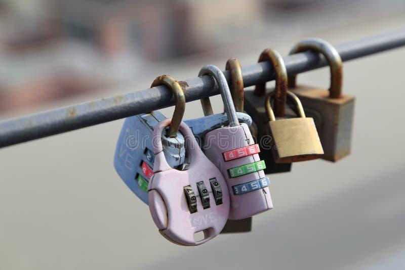 Os cadeado dos pares são fechados no trilho com fundo borrado da cidade, símbolo eterno da amizade ou amam para sempre o conceito imagens de stock royalty free