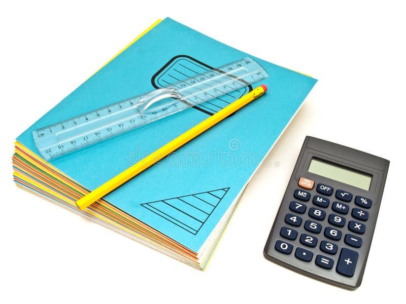 Os cadernos empilham, régua e escrevem perto da calculadora foto de stock