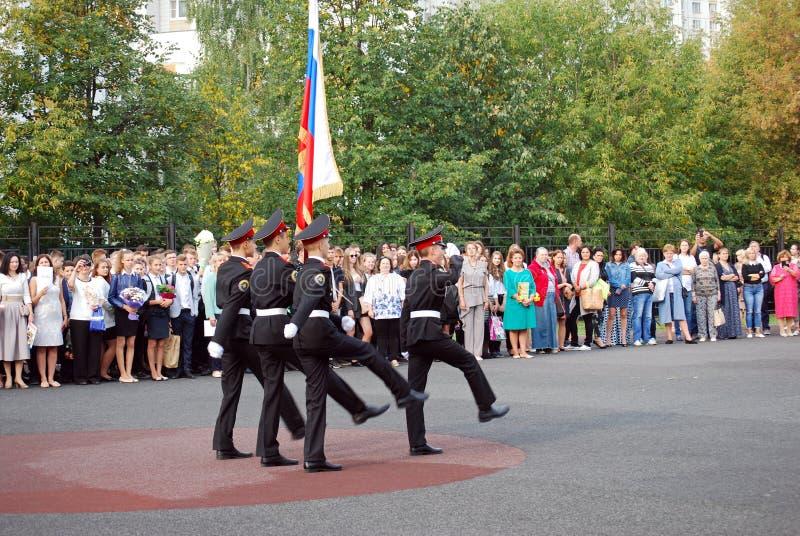 Os cadete marcham com uma bandeira em uma régua da manhã antes da escola na parada-terra Estudantes da escola fotografia de stock royalty free