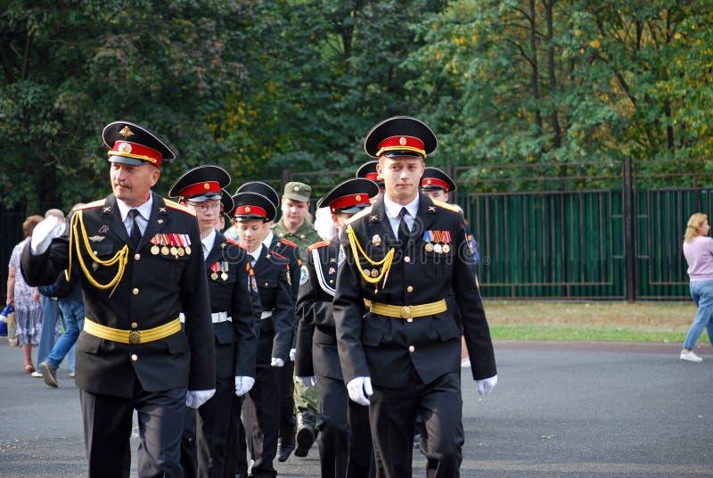 Os cadete marcham com uma bandeira em uma régua da manhã antes da escola na parada-terra Estudantes da escola foto de stock royalty free