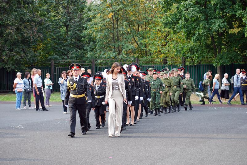 Os cadete marcham com uma bandeira em uma régua da manhã antes da escola na parada-terra Estudantes da escola imagem de stock royalty free