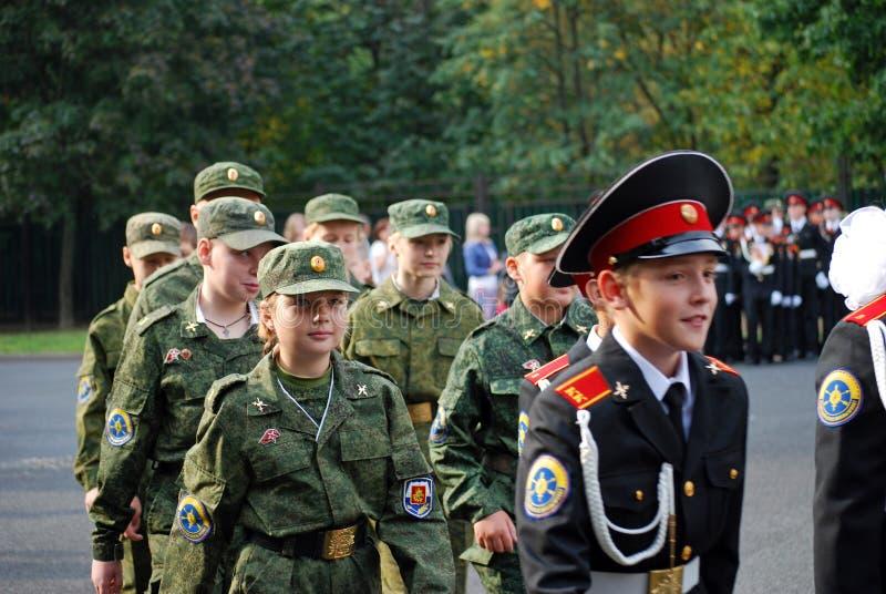 Os cadete marcham com uma bandeira em uma régua da manhã antes da escola na parada-terra Estudantes da escola fotografia de stock