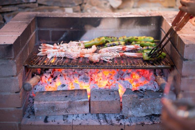 Os camarões e as pimentas grelhados giraram sobre a grade fotos de stock royalty free