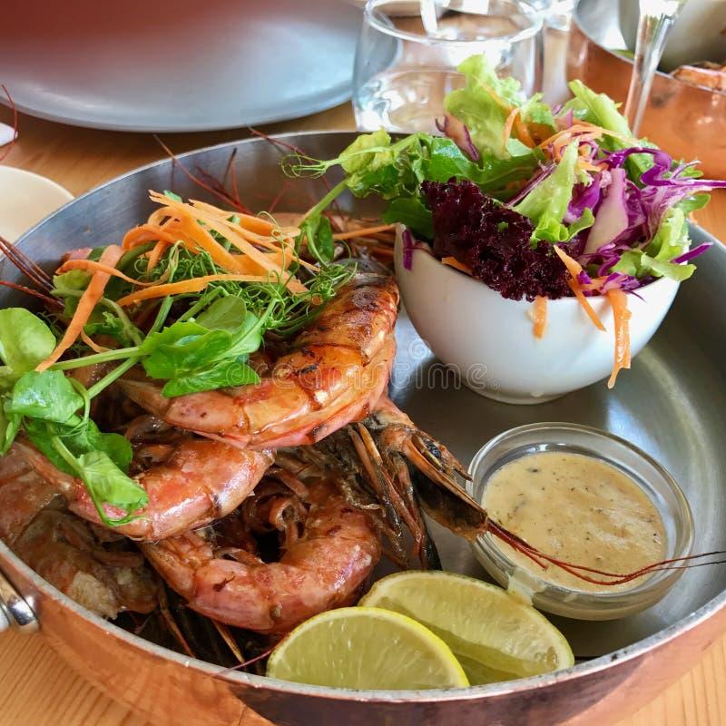 Os camarões e a salada, cal e salmouram imagens de stock