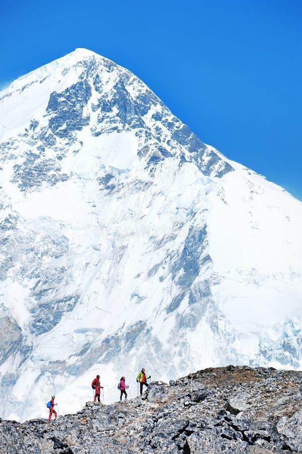 Os caminhantes com trouxas alcançam a cimeira do pico de montanha Succe foto de stock royalty free