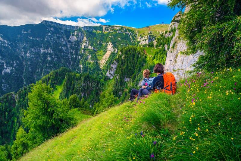 Os caminhantes da mulher ativa que relaxam nas montanhas, Bucegi, Carpathians, a Transilvânia, Romênia foto de stock