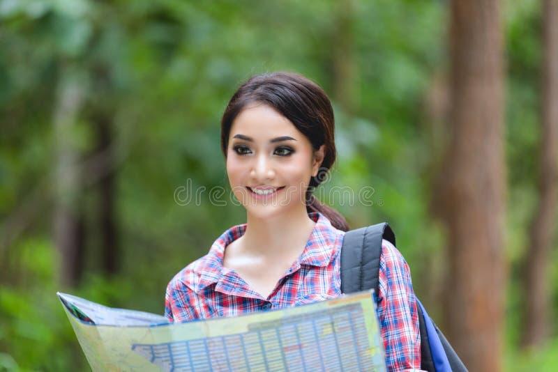 Os caminhantes das jovens mulheres que olham o mapa e relaxam o tempo no feriado concentrado foto de stock
