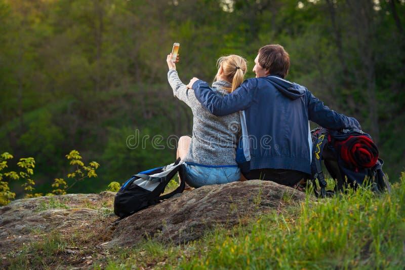 Os caminhantes novos dos pares que descansam e que apreciam a natureza bonita veem a foto de stock royalty free