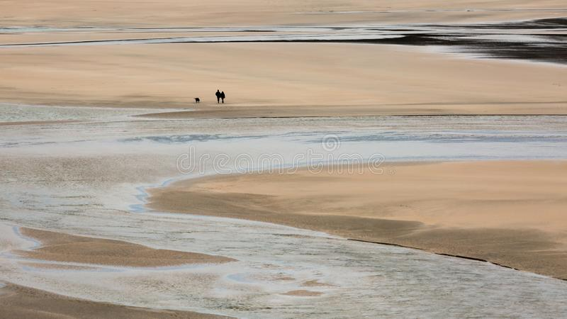 Os caminhantes solitários com o cão em Crantock encalham, Cornualha imagens de stock