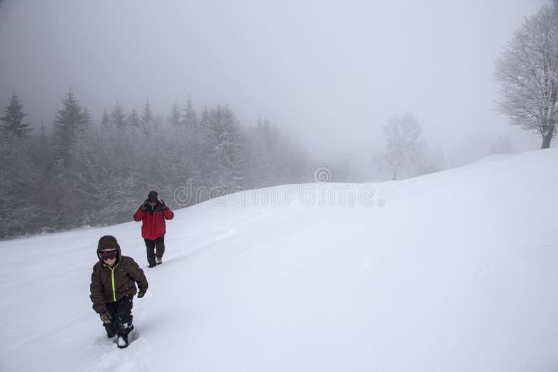 Os caminhantes vão acima na inclinação da neve no inverno Turistas que trekking em montanhas do inverno na névoa imagem de stock royalty free