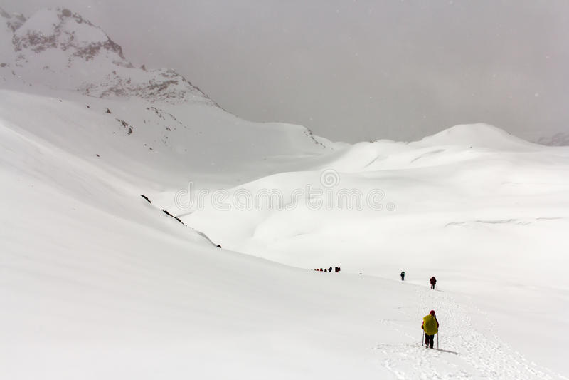 Os caminhantes vão na neve nas montanhas imagem de stock