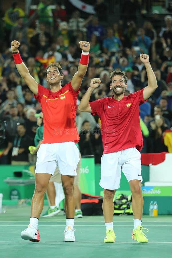 Os campeões olímpicos Rafael Nadal e Mark Lopez da Espanha comemoram a vitória no final dos dobros dos homens do Rio 2016 Olympic imagem de stock