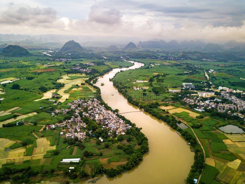 Os campos do arroz dividiram-se pelo rio na província de Guangxi, China foto de stock royalty free