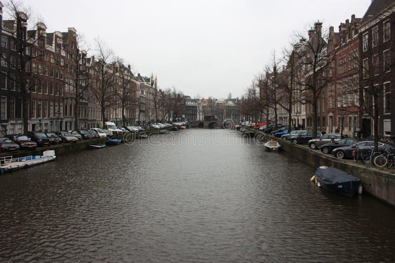 Os canais românticos de Amsterdão, dos barcos de viagem e de suas construções antigas fotos de stock royalty free