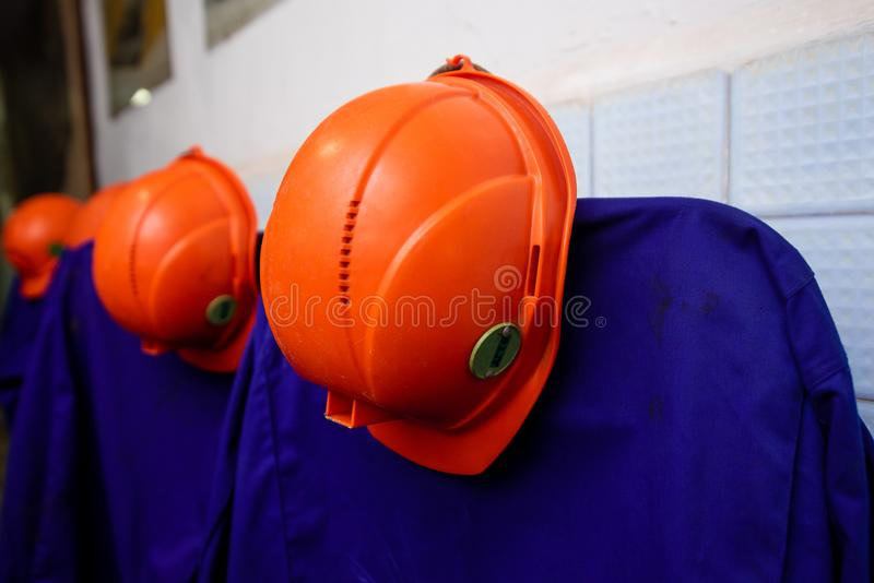 os capacetes de minera??o Alaranjado-coloridos penduram sobre vestidos protetores imagem de stock