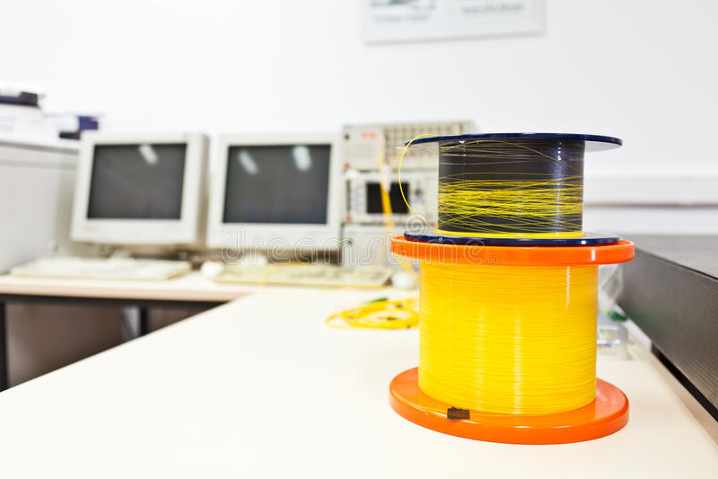 Os carretéis da fibra ótica cabografam na mesa imagem de stock