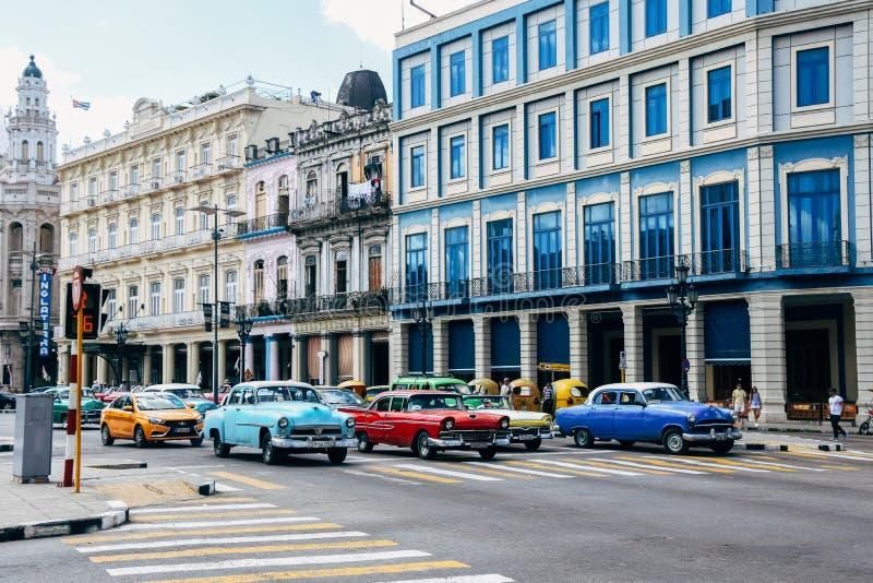 Os carros clássicos coloridos conduzem por construções coloridas velhas em Havana, Cuba foto de stock royalty free