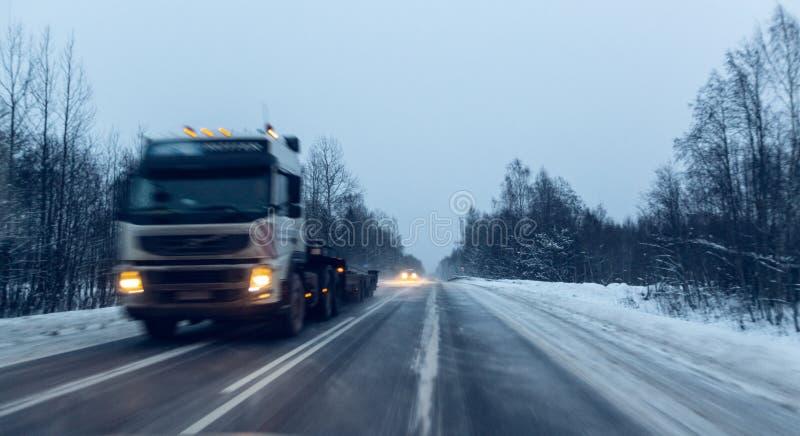 Os carros conduzem com os far?is na estrada do inverno em uma tempestade da neve no crep?sculo quando a neve est? voando Conceito imagens de stock