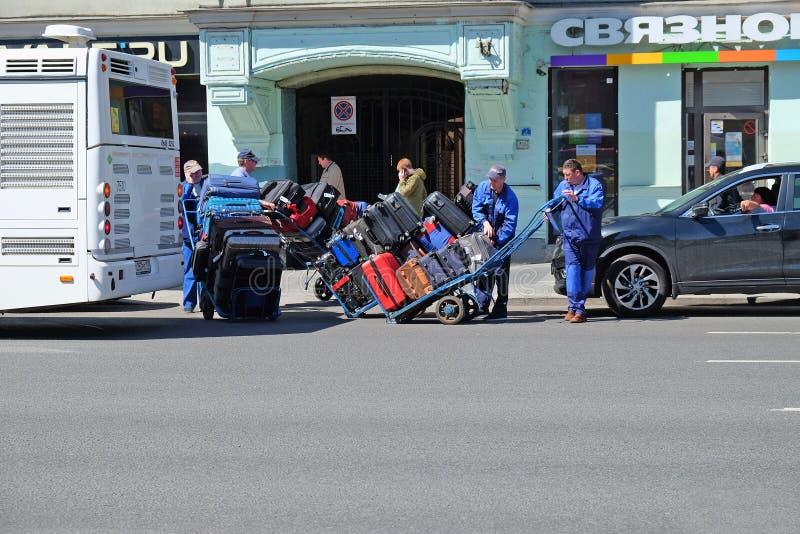 os carros conduzidos porteiros carregaram com as malas de viagem dos turistas fotografia de stock royalty free