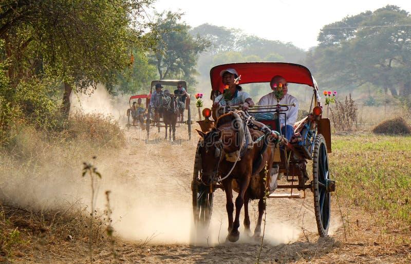 Os carros do cavalo levam turistas em Bagan, Myanmar imagens de stock
