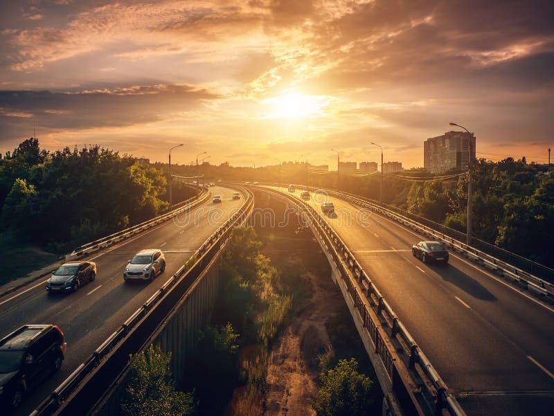 Os carros do tráfego urbano conduzem no por do sol na estrada na cena do verão da arquitetura da cidade, conceito do transporte d fotografia de stock