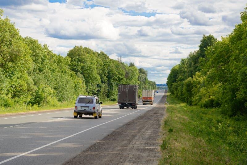 Os carros e os caminhões montam ao longo da estrada imagens de stock royalty free