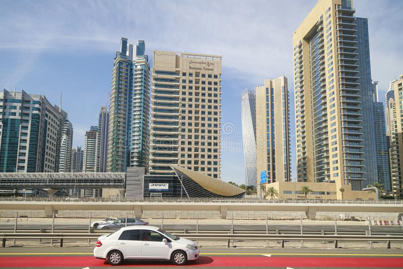 Os carros estão movendo sobre a estrada contra o contexto de prédios modernos imagem de stock