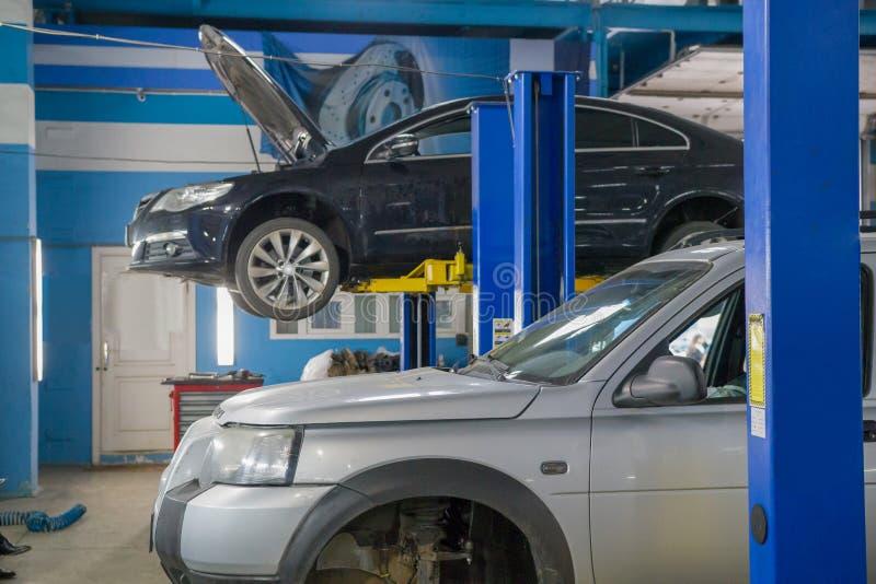 Os carros estão na oficina de reparações do carro da garagem Um dos carros é aumentado em um elevador especial fotografia de stock