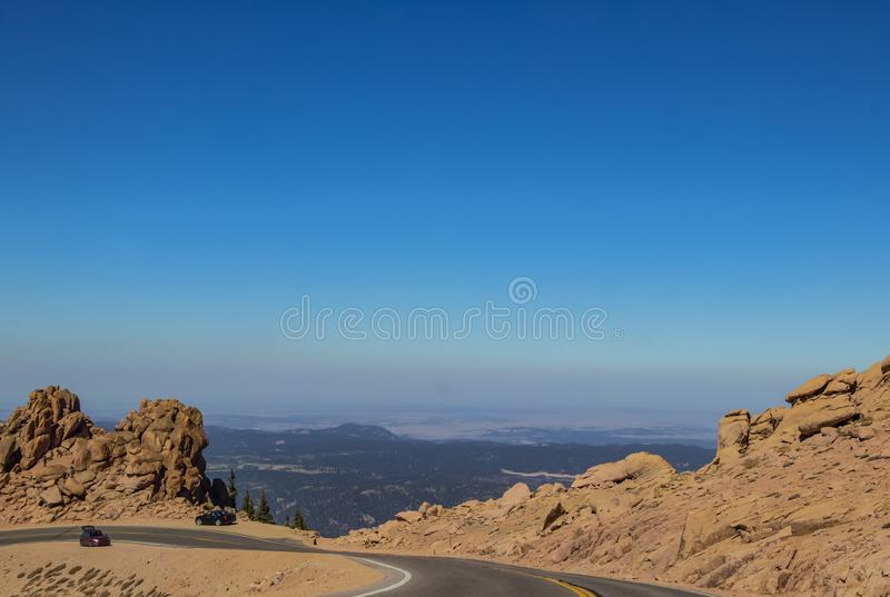 Os carros estacionaram na borda da estrada curvada da montanha acima da linha de árvore nos piques Colorado máximo com os povos q fotos de stock royalty free