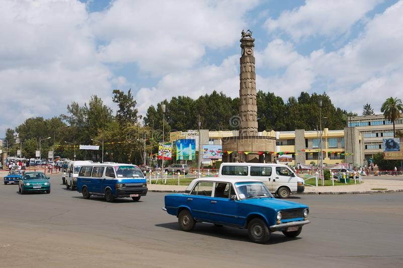 Os carros passam mas o quadrado com o monumento do quilo de Arat em Addis Ababa, Etiópia imagens de stock
