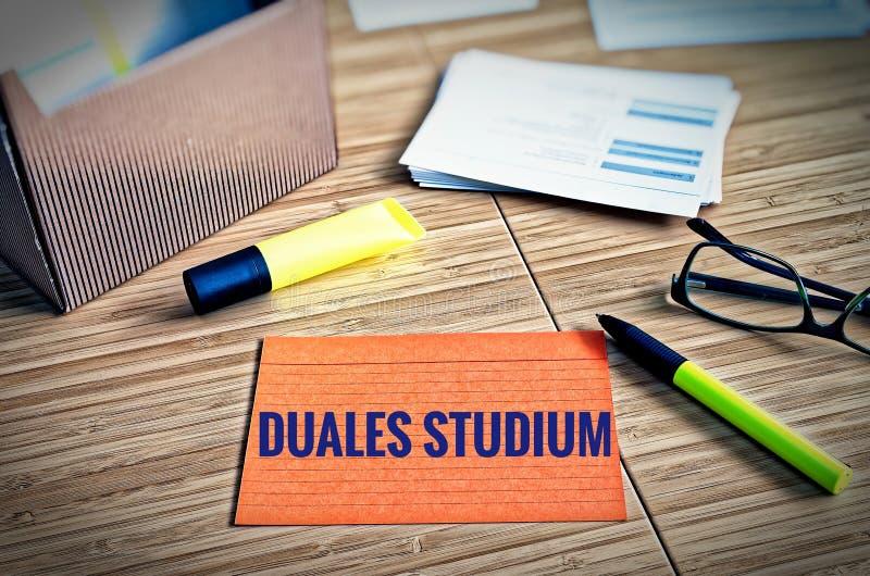 Os cartões de índice com questões legais com vidros, pena e bambu com as palavras Duales Studium do alemão em inglês dual estudo foto de stock royalty free