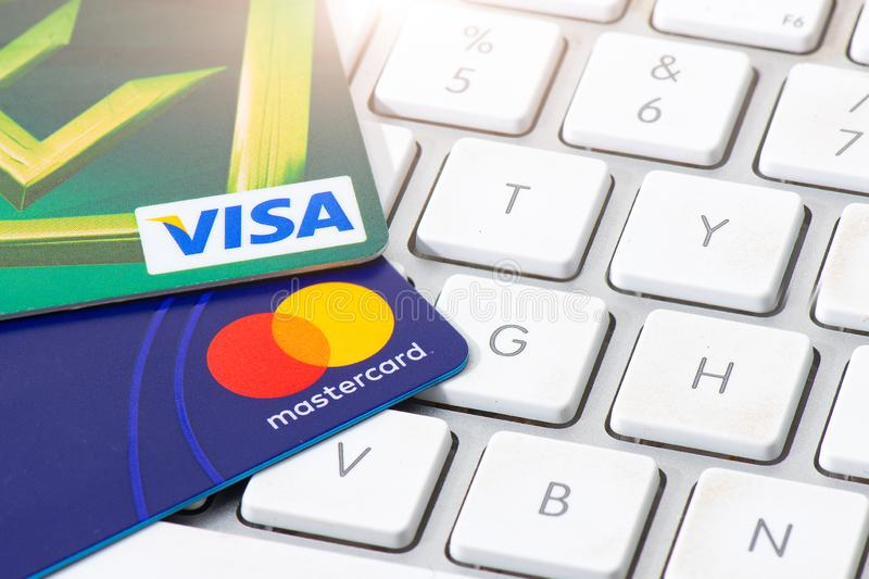 Os cartões de crédito do VISTO e do MASTERCARD apoiaram em um computador keyboar foto de stock