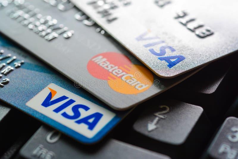 Os cartões de crédito no teclado de computador com VISTO e MasterCard marcam logotipos fotos de stock royalty free