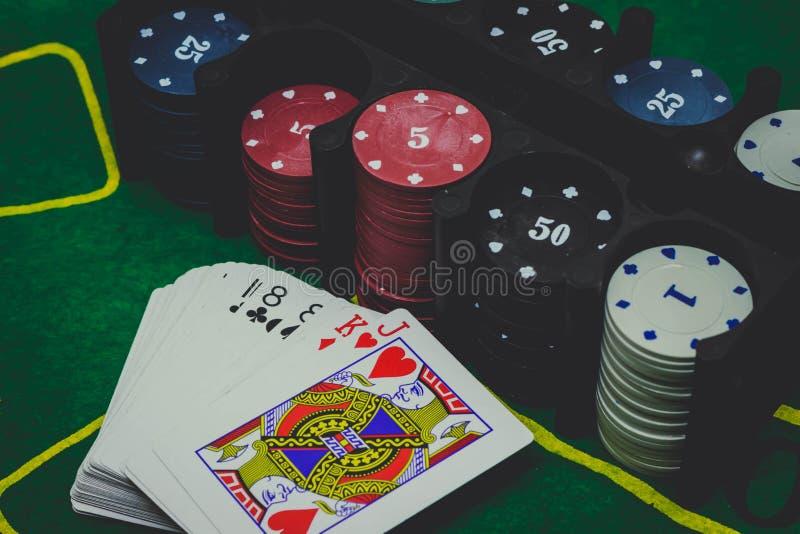 os cartões de jogo, cortam e microplaquetas de pôquer de cima no pôquer verde fotografia de stock royalty free
