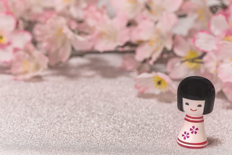 Os cartões japoneses de ano novo com boneca pequena Kokeshi com flor p fotos de stock royalty free