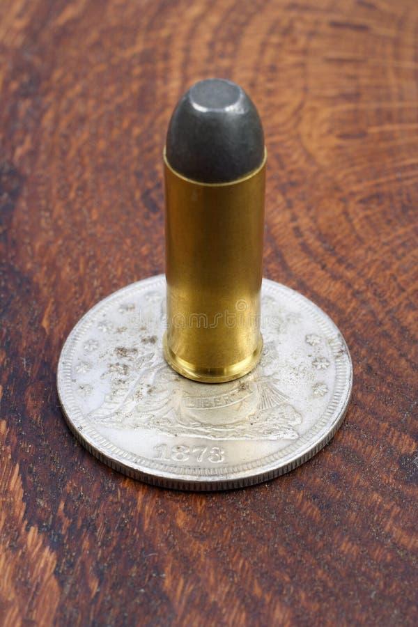 Os cartuchos do revólver e o período ocidental selvagem do dólar de prata no fundo de madeira fotografia de stock royalty free
