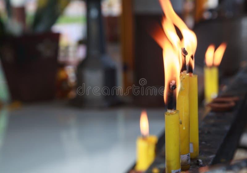 Os castiçal amarelos iluminaram-se na prateleira da oração no santuário do templo budista Budismo, cerimônia religiosa tradiciona fotos de stock royalty free
