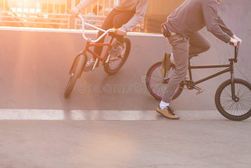 Os cavaleiros de Bmx fazem truques em um parque do patim no fundo do por do sol Nivelando ciclistas de formação de BMX Conceito d foto de stock
