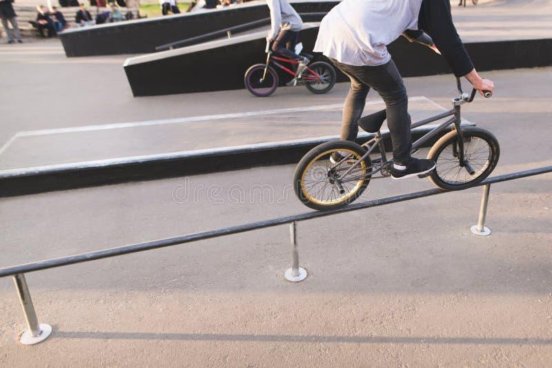 Os cavaleiros de BMX montam um parque do patim em uma bicicleta e fazem truques Conceito de BMX foto de stock royalty free