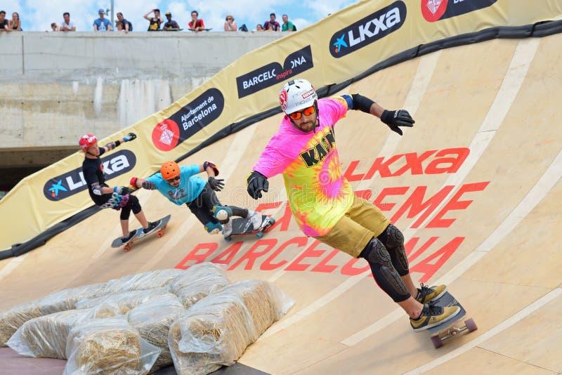 Os cavaleiros profissionais no Longboard cruzam a competição em jogos extremos de Barcelona dos esportes de LKXA fotos de stock