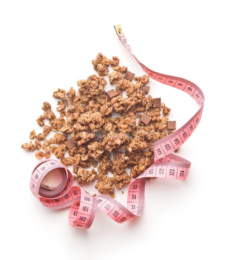 Os cereais de café da manhã do granola e a fita de medição imagem de stock royalty free