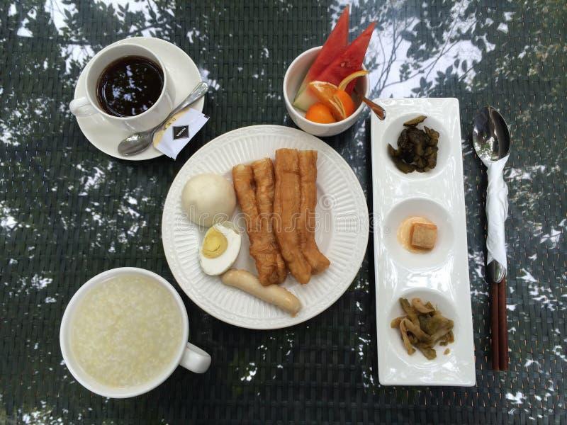 Os chineses tomam o café da manhã em uma tabela em um jardim do hotel na cidade de Xiamen, China imagens de stock royalty free