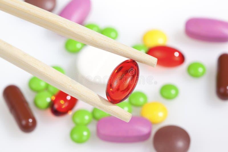 Os Chopsticks mantêm um comprimido vermelho brilhante fotos de stock royalty free