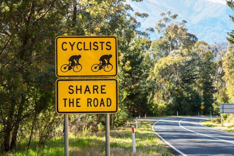 Os ciclistas compartilham do sinal de estrada imagem de stock