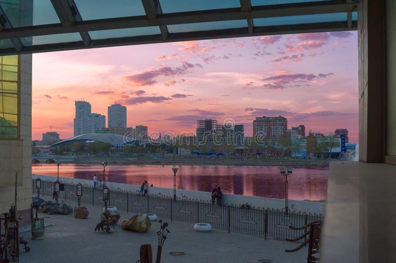 Os cidadãos admiram o por do sol, que é refletido no rio de Miass foto de stock