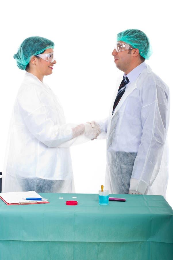 Os cientistas dão o aperto de mão em um laboratório fotos de stock