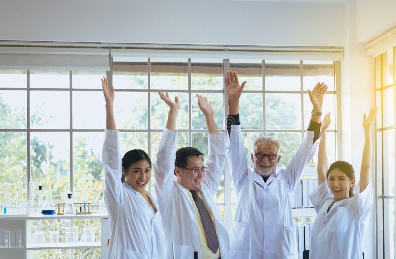 Os cientistas entregam aumentaram acima, grupo de trabalhos de equipe dos povos da diversidade no laboratório, no trabalho do suc imagem de stock royalty free