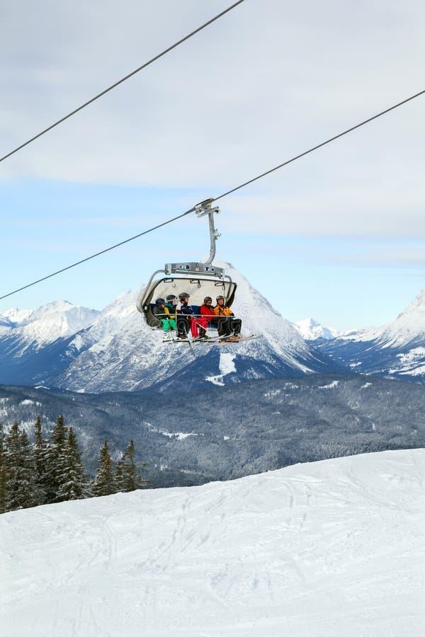 Os cinco esquiadores ascensão pelo elevador de cadeira foto de stock royalty free