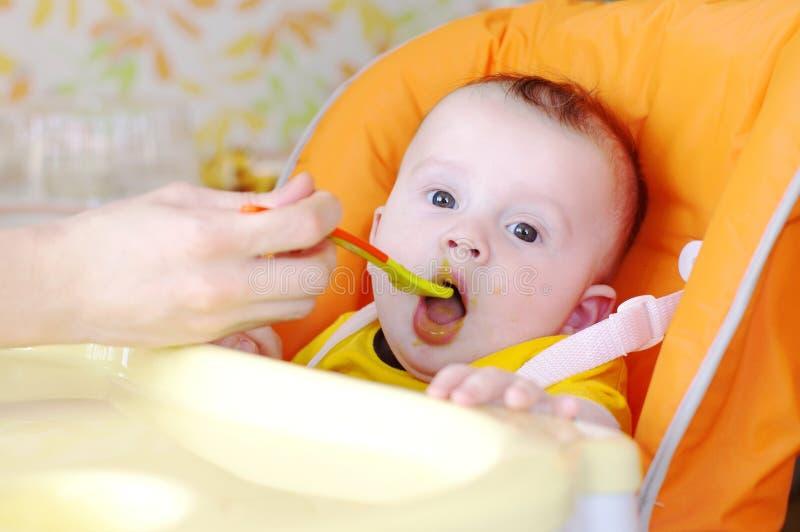 os Cinco-meses do bebê são alimentados pelo purê,puré de uma colher fotos de stock